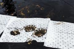 Papier absorbant utilisé pour rayer l'huile du pétrole brut renversé image libre de droits