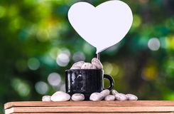 Papier auf einer Kaffeetasse mit Stein auf einem hölzernen Brett und einem Bokeh-Baumhintergrund Lizenzfreie Stockfotografie