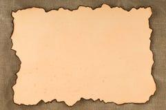 Papier avec des bords de brûlure sur la toile Photo stock