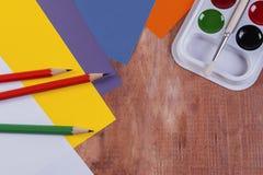 Papier-, Bürsten- und Aquarellfarbe auf einem hölzernen Hintergrund Stockfotografie