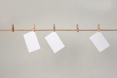 Papier blanc de photo Accrocher sur une corde à linge avec des pinces à linge Photographie stock libre de droits