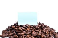 Papier bleu vide de post-it sur la pile des grains de café rôtis Images stock