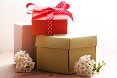 Papier-boxex und Blumen auf Holztisch Lizenzfreie Stockfotografie