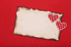 Papier brûlé par grunge blanc et deux coeurs Image stock