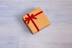 Papier cadeau, atado con un arco, en un fondo azul Fotos de archivo libres de regalías