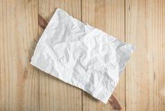 Papier chiffonné par blanc sur le fond en bois Photo stock