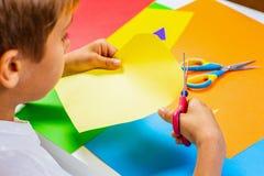 Papier coloré de coupe d'enfant avec des ciseaux à la table image libre de droits