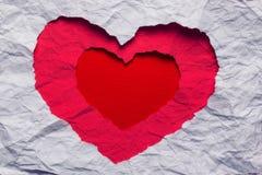 Papier déchiré blanc dans le symbole de forme de coeur Photos stock