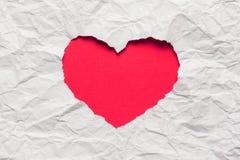 Papier déchiré blanc dans le symbole de forme de coeur Images libres de droits