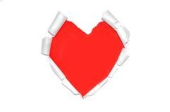 Papier déchiré blanc dans le symbole de forme de coeur au-dessus du rouge Photographie stock