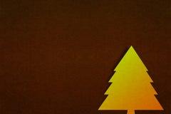 Papier d'arbre de Noël d'or avec le fond de papier de brun foncé photos libres de droits