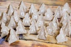Papier d'emballage fait main d'arbres de Noël de calendrier d'avènement de Noël avec des nombres à l'arrière-plan en bois Photos stock