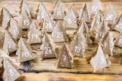 Papier d'emballage fait main d'arbres de Noël de calendrier d'avènement de Noël avec des nombres à l'arrière-plan en bois Photos libres de droits