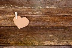 Papier de Brown - coeur de carton sur la pince à linge sur la ficelle sur rustique Image libre de droits