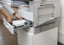 Papier de chargement d'homme dans le plateau du photocopieur au bureau photo libre de droits