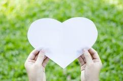Papier de coeur de prise de main Images stock