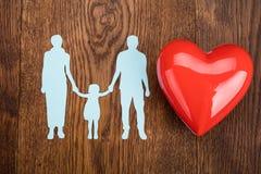 Papier de famille coupé avec le coeur rouge sur le bureau Photographie stock