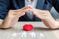 papier de famille de couverture de mains et coeur rouge Concept de soins de santé et d'assurance photos stock