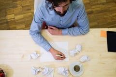 Papier de froissement de concepteur à son bureau Images stock