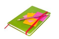 Papier de note avec le crayon sur le cahier Photo stock