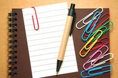 Papier de note avec le stylo et trombones sur le carnet Photographie stock libre de droits