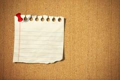 Papier de note blanc avec la broche sur le panneau de liège Photos stock