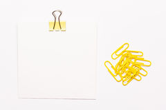 Papier de note blanc et trombones jaunes Photos stock