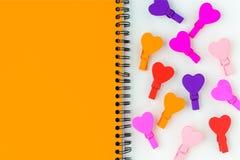 Papier de note jaune et beaucoup de coeurs en bois colorés Images libres de droits