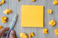 Papier de note jaune vide avec le stylo de participation d'homme d'affaires et papier emietté sur le fond en bois de table L'espa images stock