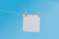 Papier de note vide chevillé sur la corde à linge contre le ciel bleu Images libres de droits