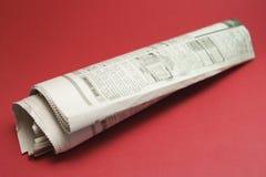 Papier de nouvelles de roulis sur le rouge Images stock