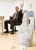 Papier de projection d'homme d'affaires dans le panier de détritus Photos stock