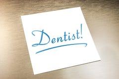 Papier de Sticky Note On de dentiste se trouvant sur l'aluminium d'or Image libre de droits