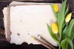 Papier de vintage, crayons et tulipes jaunes sur le fond en bois L'espace libre pour votre texte Photo stock