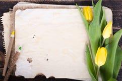 Papier de vintage, crayons et tulipes jaunes sur le fond en bois L'espace libre pour votre texte Photos libres de droits