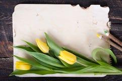 Papier de vintage, crayons et tulipes jaunes sur le fond en bois L'espace libre pour votre texte Image stock