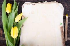 Papier de vintage, crayons et tulipes jaunes sur le fond en bois L'espace libre pour votre texte Photographie stock libre de droits