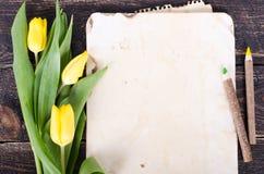 Papier de vintage, crayons et tulipes jaunes sur le fond en bois L'espace libre pour votre texte Images stock