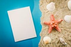 Papier et coquilles sur le sable Photos libres de droits