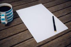 Papier et fontaine par la tasse de café Image stock