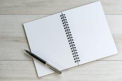 Papier et stylo de note vides blancs s'ouvrants du côté gauche avec sur la lumière photographie stock libre de droits