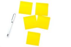 Papier et stylo de notes jaunes sur le fond blanc Images libres de droits