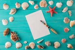 Papier für Anmerkungen nähern sich Muscheln auf hölzernem Hintergrund Kopieren Sie Platz Lizenzfreies Stockfoto