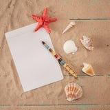 Papier für Anmerkungen nahe Muscheln auf Sandhintergrund Kopieren Sie Platz Stockfotos