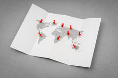 Papier gefaltete Weltkarte mit rotem Pin Pointer Lizenzfreie Stockfotografie