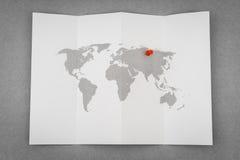 Papier gefaltete Weltkarte mit rotem Pin Pointer Stockbilder