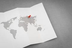Papier gefaltete Weltkarte mit rotem Pin Pointer Stockfotografie