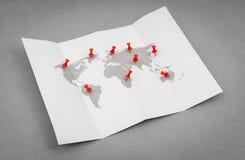 Papier gefaltete Weltkarte mit rotem Pin Pointer Lizenzfreie Stockfotos