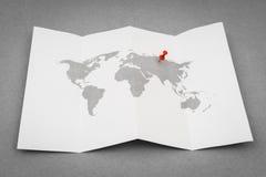 Papier gefaltete Weltkarte mit rotem Pin Pointer Stockfotos