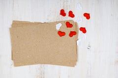 Papier, Geschenk und Herzen auf einem hölzernen Hintergrund Lizenzfreie Stockfotos